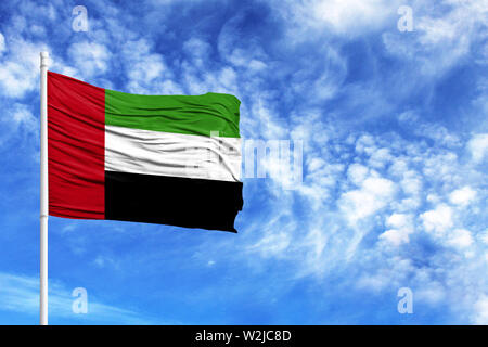 National flag of United Arab Emirates on a flagpole in front of blue sky - Stock Photo