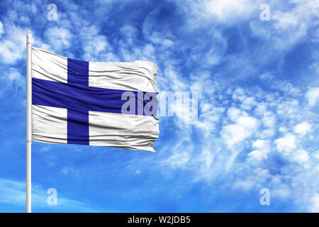National flag of Finland on a flagpole in front of blue sky - Stock Photo