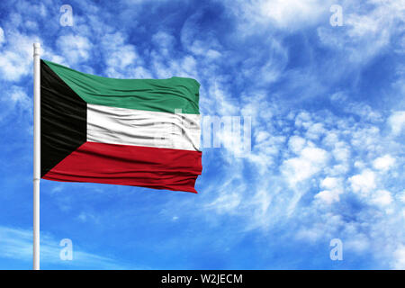 National flag of Kuwait on a flagpole in front of blue sky - Stock Photo