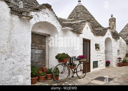 Amazing old trulli houses on the cloudy sky background in Alberobello town in Italy. There are many colorful flowers in the pots, vintage bicycle near - Stock Photo