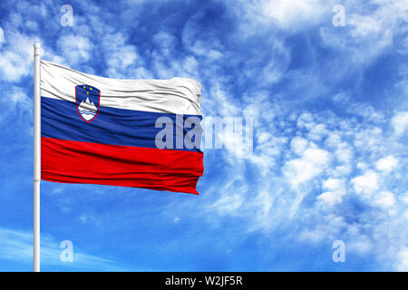 National flag of Slovenia on a flagpole in front of blue sky - Stock Photo