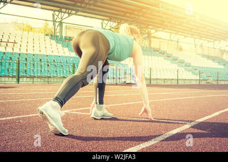 Ready to go. Young fitness girl wearing blue top, black tights, sneakers and pony-tail on the starting line of stadium track, preparing for a run - Stock Photo