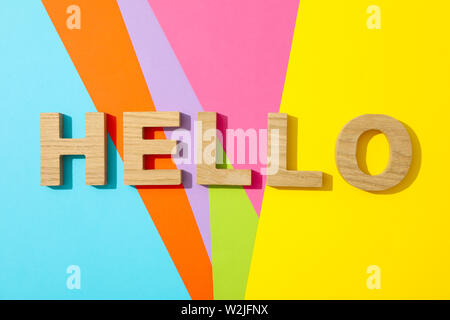 Word Hello lined with wooden letters on multicolor background - Stock Photo