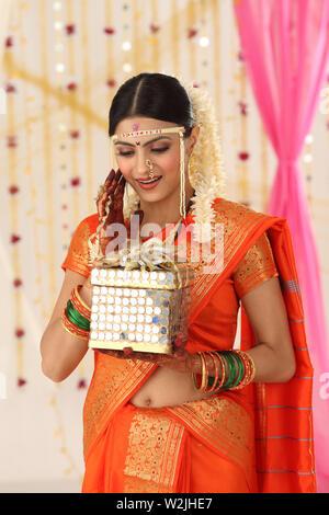 Indian bride holding gift box - Stock Photo