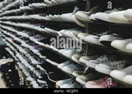Side view of shoe store shelves with of lots of sneakers on sale. Low-budget comfortable footwear shopping. Unisex stylish teenager shoes. Rows of new - Stock Photo