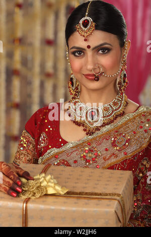 Indian bride holding gift boxes and smiling - Stock Photo