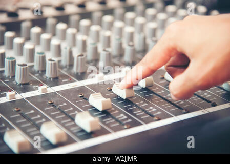 Hands of sound engineer working on recording studio mixer. Expert adjusting the volume of a voice, mixing console with mixer board. - Stock Photo