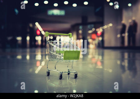 Conceptual shot of a small shopping cart put on the floor at blur background of shopping centre. Petty expenses in supermarket. Going for stuff in - Stock Photo