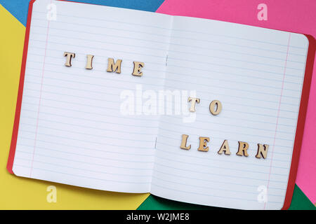 Time to learn, text in an open notebook, colored paper sheets. Concept of education, starting school, back to school. Colorful background - Stock Photo