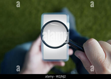 Close up of male hands holding smartphone with magnifying glass above the device screen. Shot of a sitting person with mobile in one hand and the - Stock Photo