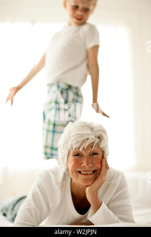 Mature woman smiles and rests her head on her hand as she lies on her front with her young grandson standing on the bed behind her as they pose for a portrait. - Stock Photo