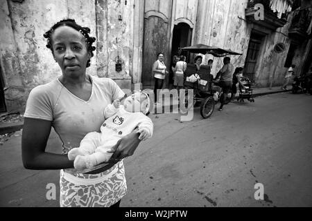 A woman holds the baby of a friend in Havana. - Stock Photo