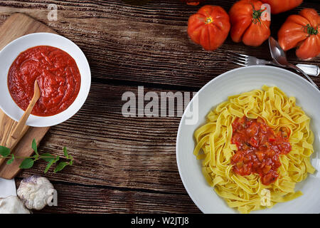 Homemade tagliatelle with homemade ratatouille sauce. Half-made pasta, fresh tomatoes, fresh eggs, garlic, salt, oregano, pepper and basil. - Stock Photo
