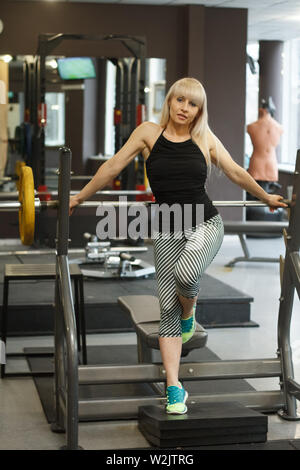 A Young athletic blonde is leaning on a barbell and looking at the camera in the gym, the concept of a healthy sports life - Stock Photo
