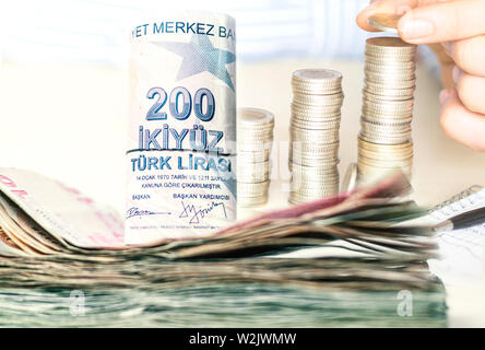 stacked turkish lira banknotes and coins - Stock Photo