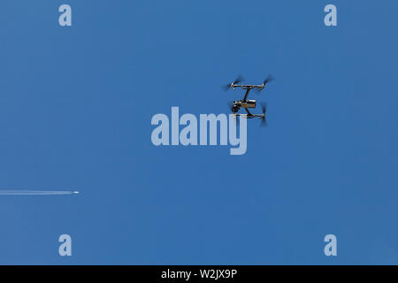 Color image of a quadrocopter against a blue sky. Drone hovers in the air - Stock Photo