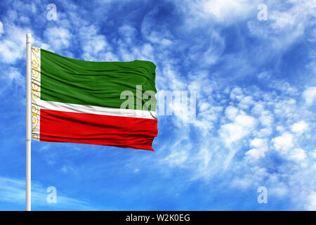 National flag of Chechen Republic on a flagpole in front of blue sky - Stock Photo