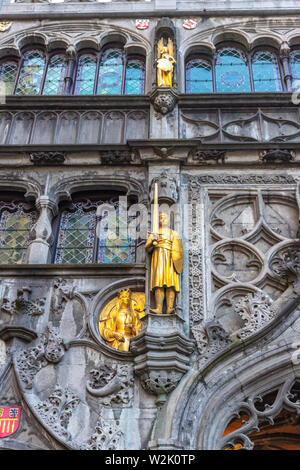 Gilded statue of warrior in body armour holding sword and shield on facade of XII century Roman Catholic Basilica of the Holy Blood in Bruges, Belgium - Stock Photo