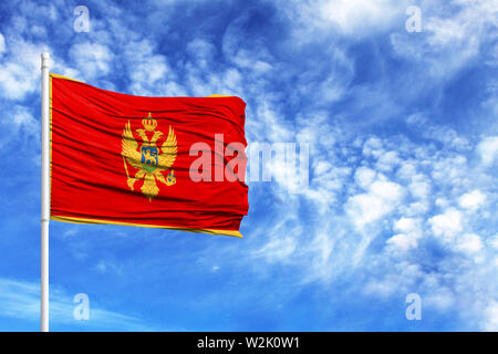 National flag of Montenegro on a flagpole in front of blue sky - Stock Photo