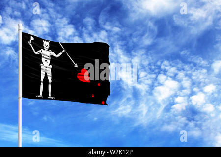 National flag of Blackbeard Pirate on a flagpole in front of blue sky - Stock Photo