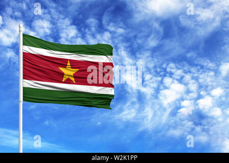 National flag of Suriname on a flagpole in front of blue sky - Stock Photo