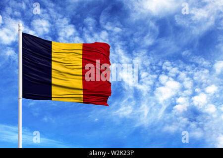 National flag of Chad on a flagpole in front of blue sky - Stock Photo
