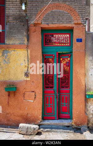 Old grunge decorated door painted in green and red vibrant colors on orange painted stone wall, Old Cairo, Egypt - Stock Photo