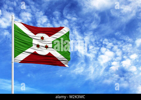 National flag of Burundi on a flagpole in front of blue sky - Stock Photo