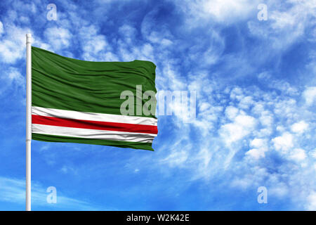 National flag of Chechen Republic of Ichkeria on a flagpole in front of blue sky - Stock Photo