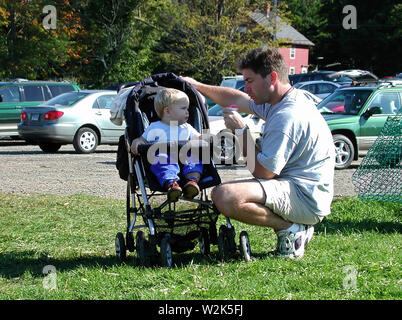Middlefield, CT USA. Sept 2016. Young son in stroller waiting for dad to take first dibs on his sweet snow cone. - Stock Photo