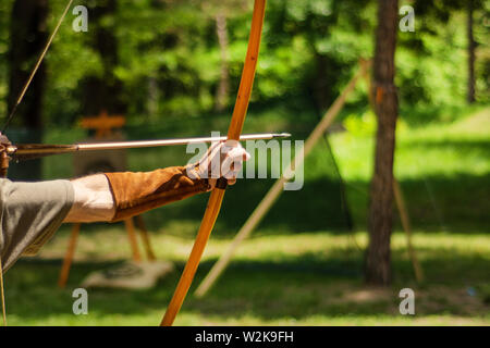 Man medieval archer hand holds his bow with an arrow and aiming at the target outdoor activity in the forest. Medieval sport concept. Close up