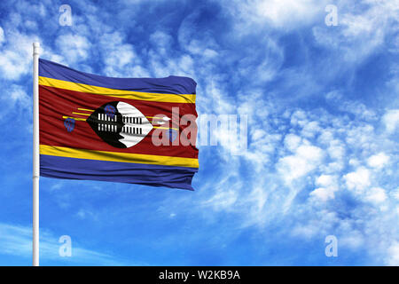 National flag of Swaziland on a flagpole in front of blue sky - Stock Photo