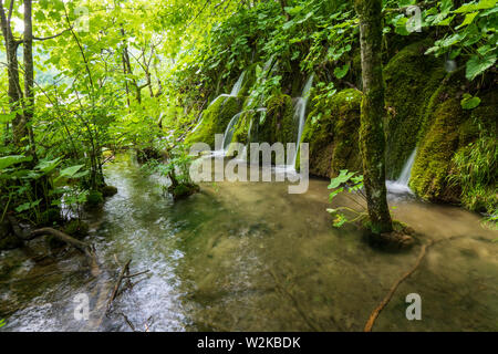 Small cascades of fresh water rushing down mossy rocks at the Plitvice Lakes National Park in Croatia - Stock Photo