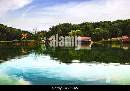 Landscape panorama with windmills and lake - Stock Photo