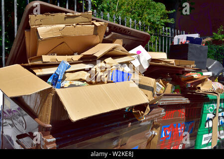 Overflowing large recycling and rubbish bins - Stock Photo