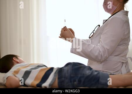 A doctor with a syringe in his hands is preparing for an injection. Baby lay on his stomach, turned his head to the side of the needle. - Stock Photo