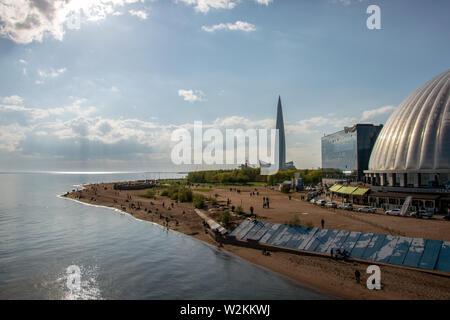 Photo of beach and the embankment of the Neva Bay in the park named after the 300th anniversary of St. Petersburg overlooking the Lakhta Center - Stock Photo