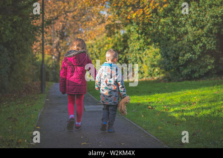 Boy holding hs favourite teddy bear soft toy holding hands with his sister and walking together on a path in the countryside in autumn - Stock Photo