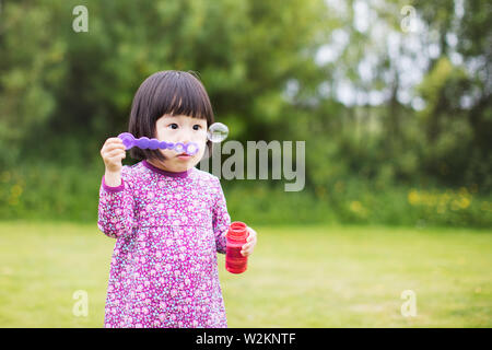 toddler girl  blowing soap bubbles at summer home garden - Stock Photo