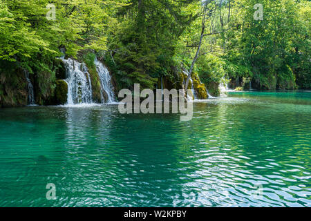 Rushing water cascades down the natural barriers into the crystal clear and azure coloured Lake Kozjak at the Plitvice Lakes National Park, Croatia - Stock Photo