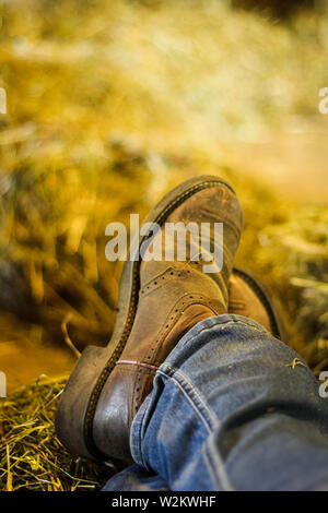 Cowboy boots resting in the hay loft - Stock Photo