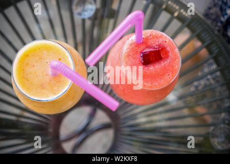 Freshly blended fruit smoothies of various colors and tastes in glass jars. Fresh juice Yellow, red. Drinking juice outdoor. Summer drinks for kids - Stock Photo