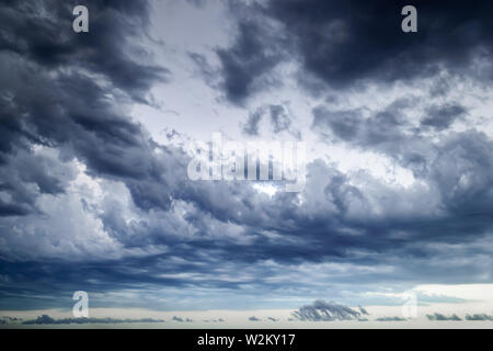 Background of dark stormy sky at summer evening. Dramatic skyscape with large gray clouds. Different cloud types and atmospheric phenomena. - Stock Photo