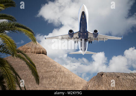 Bottom View of Passenger Airplane Flying Over Tropical Palm Trees and Huts. - Stock Photo