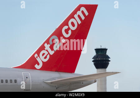 The tailfin of a Jet2 airliner taxiing along the runway in front of the control tower at Manchester Airport. - Stock Photo