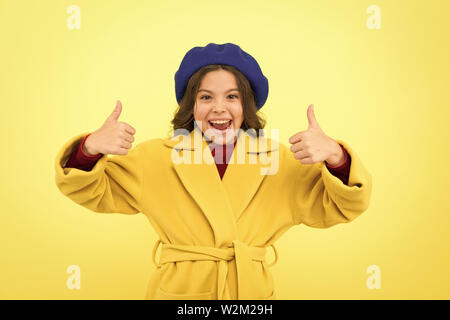 Child promoting something yellow background. Girl show thumbs up gesture. Advertising product. Look at this. Advertisement launching product. Advertisement concept. Place for ad advertisement. - Stock Photo