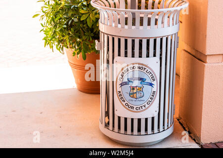 Fort Myers, USA - April 29, 2018: City town street in Florida gulf of mexico coast and closeup of trash can with sign by shopping and restaurants stor - Stock Photo