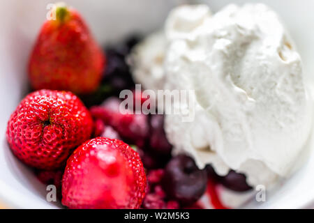 Macro closeup of colorful bowl of vanilla ice cream topped with fresh red strawberry large berries - Stock Photo