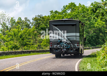 Luray, USA - June 1, 2019: View of road with rv trailer leading to forest in Shenandoah Blue Ridge appalachian mountains on skyline drive - Stock Photo