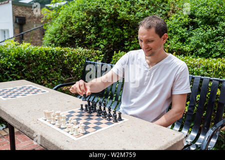Chess table in park in Hot Springs, Arkansas with man playing during summer day sitting on bench - Stock Photo